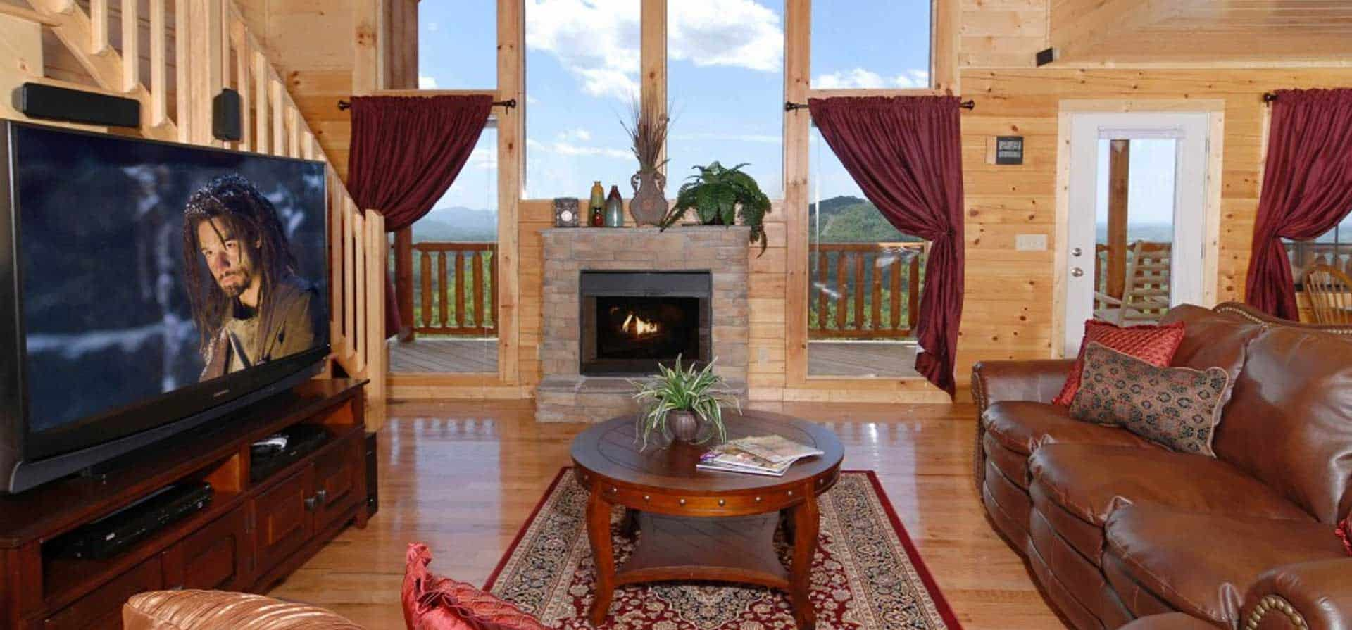 A cozy living room with large screen TV and mountain view in our 1 Bedroom Cabins