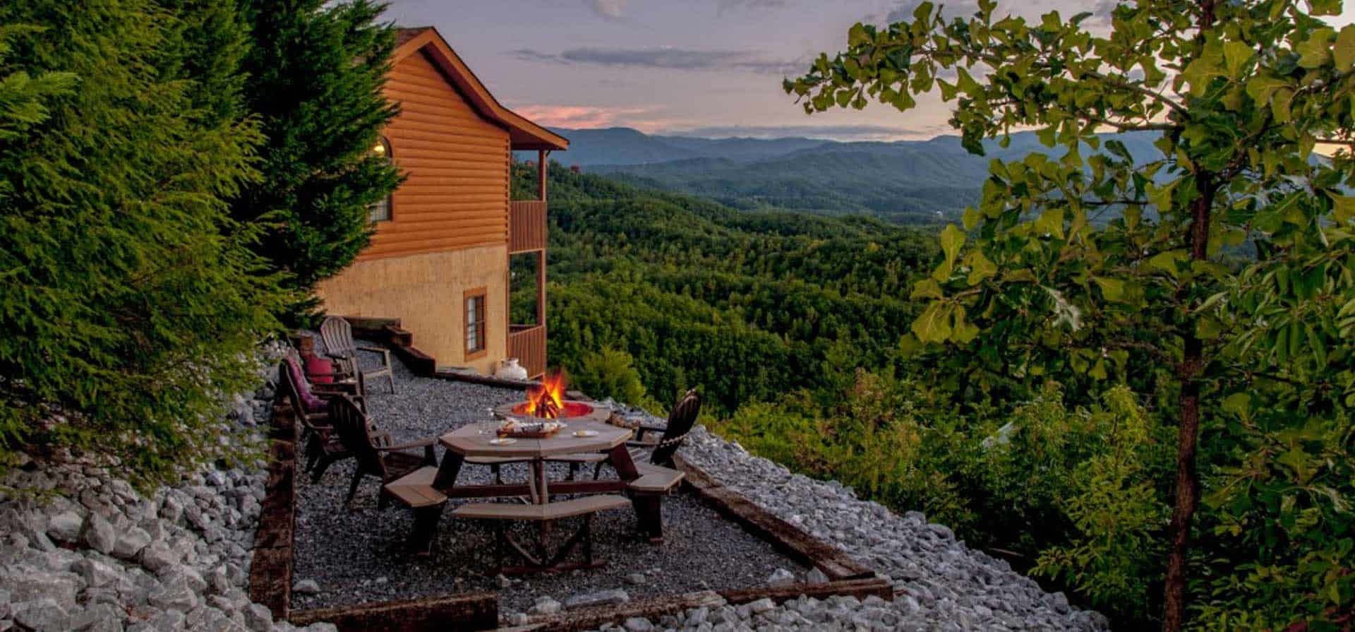 A fire pit surrounded by chairs with mountain view at one of 3 Bedroom Cabins