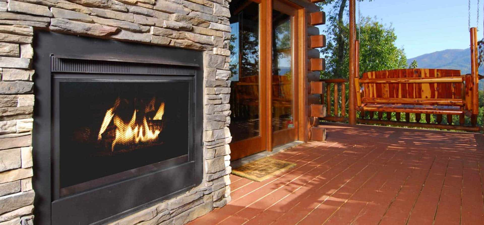 A beautiful fireplace and swing on the deck of one of Pigeon Forge Cabins